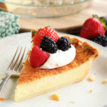 Slice of Buttermilk Pie with whipped topping and fruit on top