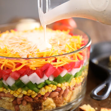 Layered Cornbread Salad in clear glass bowl - buttermilk ranch being poured over the top