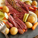 Slow cooker corned beef and cabbage in blue serving dish