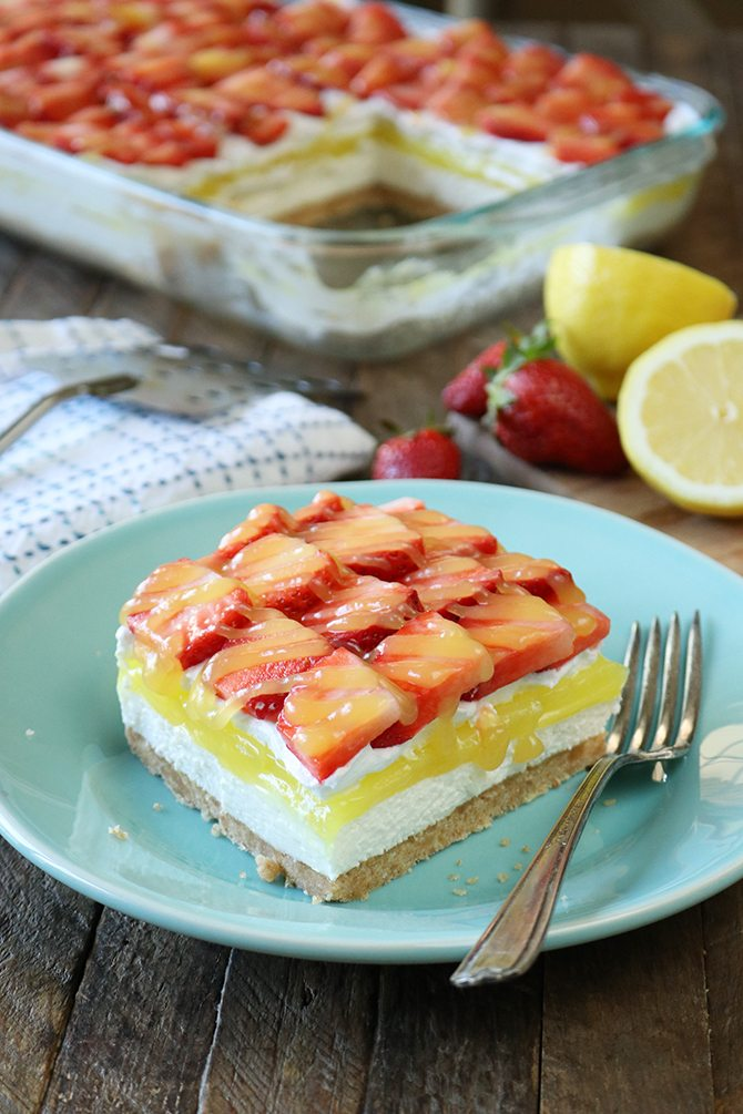 This recipe for Strawberry lemon Lush is sure to be your new favorite layered dessert! A Nilla Wafer crust topped with a layer of sweetened cream cheese, lemon pie filling, whipped topping, and it's all topped off with fresh strawberries drizzled in lemon curd!