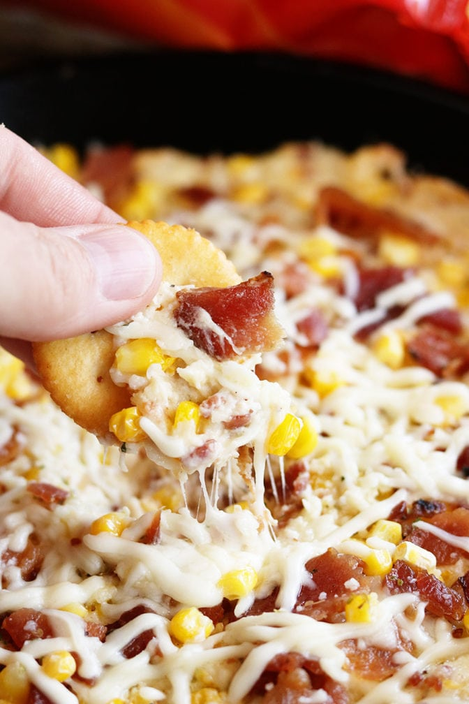 Cheese Bacon Corn dip being dipped with cracker