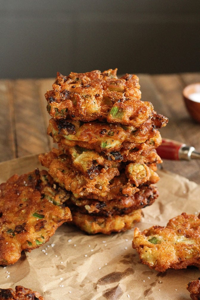 Okra and Green Tomato Fritters stacked on brown parchment paper