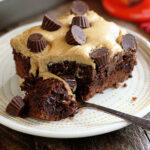 Chocolate Peanut Butter Poke Cake on plate with spoon