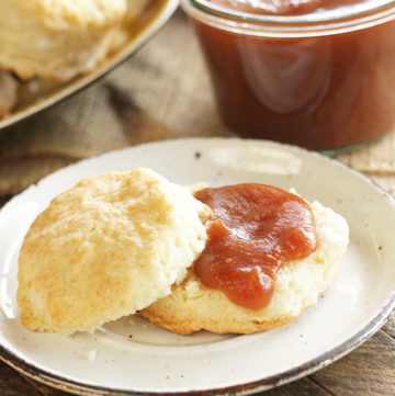Slow Cooker Apple Butter on biscuit on white plate