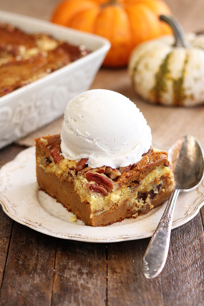 Pumpkin Spice Dump Cake on white serving dish with ice cream on top