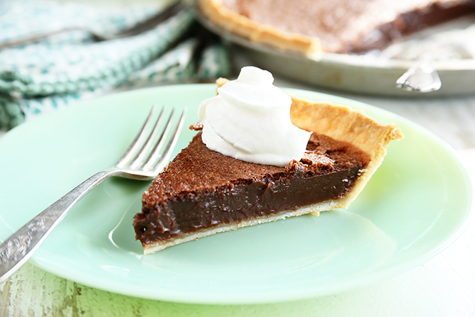 Chocolate Chess Pie served in plate with whipped topping