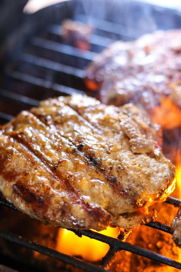 Cheesy spiced pork burgers on being cooked on grill