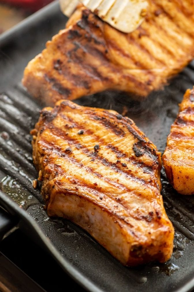Pork chops being cooked on grill