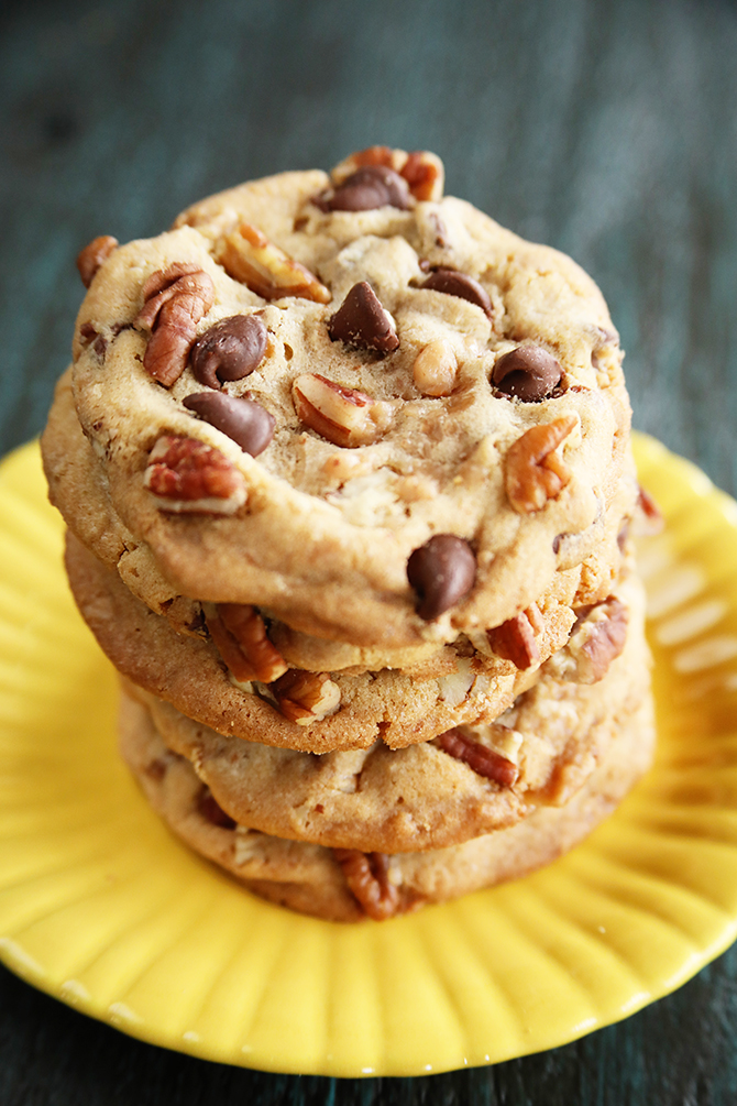 Chocolate Chip toffee Pecan Cookies stacked on yellow plate