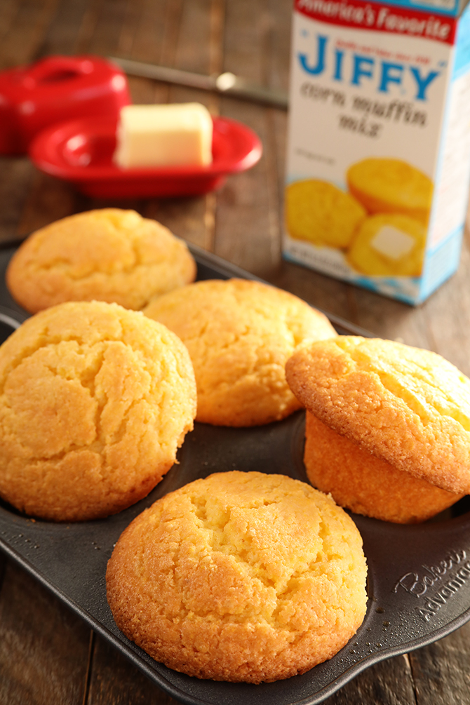 Jiffy Cornbread Muffins in a muffin pan with a box of Jiffy corn mix behind them