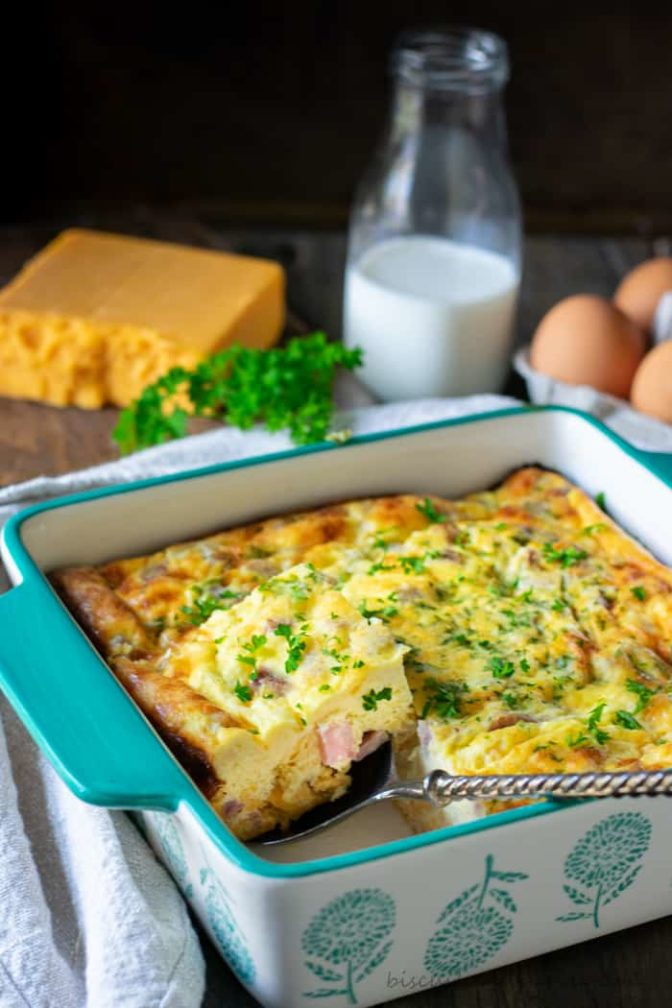 Keto Ham Casserole in a blue and white casserole dish with a block of cheese and bottle of milk and a few eggs behind it
