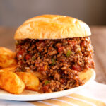Creole Sloppy Joes  on a white plate with potato wedges