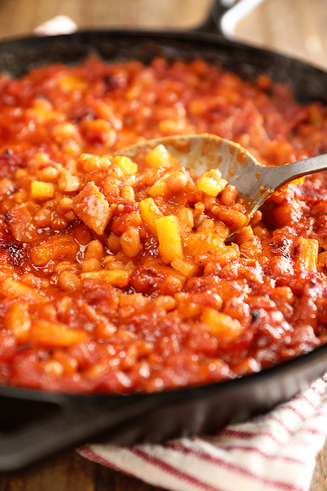 Spoonful of Bacon Pineapple Baked Beans in a cast iron skillet