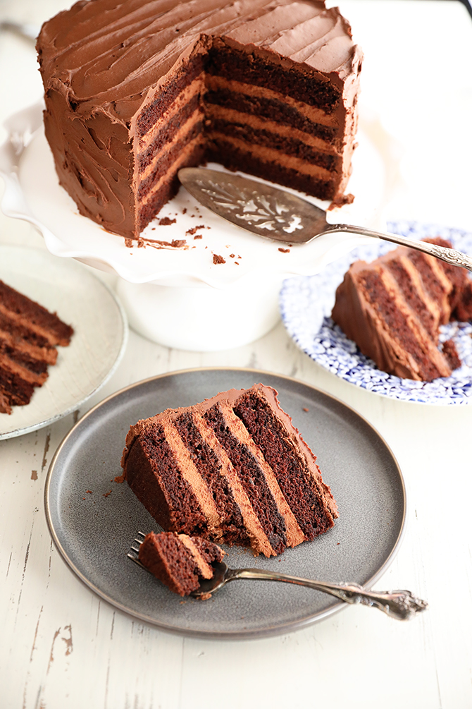 Slices of Triple Chocolate Mousse Cake on plates with large cake in the background