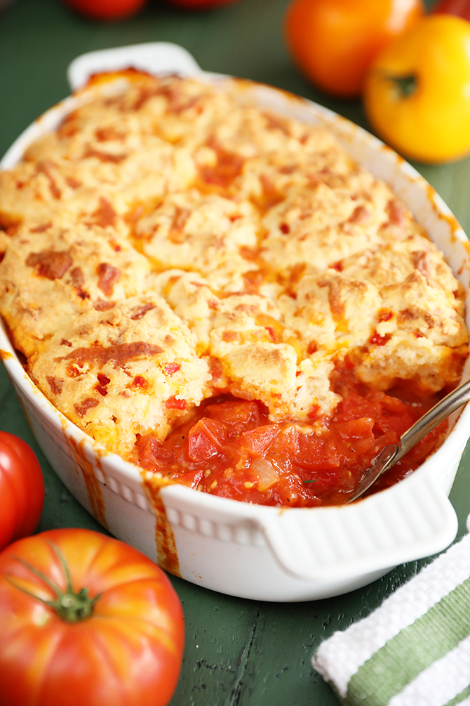Baking dish with tomato cobbler topped with biscuits